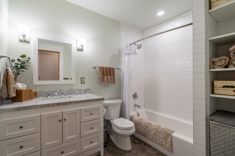 upgraded modern powder room with subway tile shower, chrome faucet, open shelving, updated vanity and finishes