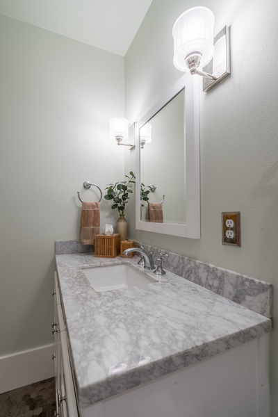 upgraded minimalist powder room with updated vanity, chrome faucet and modern finishes