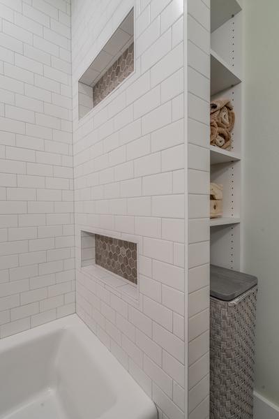 upgraded modern bathroom, subway tile shower, inset shower shelves, open shelving linen storage