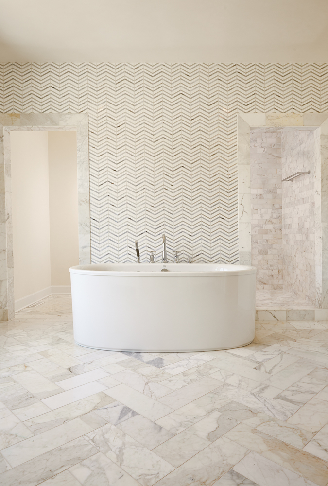 all beige tile bathroom. stone herringbone floor and chevron glass tile walls