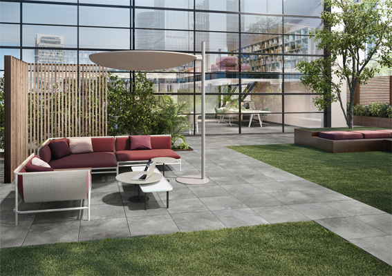 outdoor patio space at a large corporate headquarters. Gray square tiles lining the paths in and out of the commercial building with a comfortable patio space for socializing in the middle.