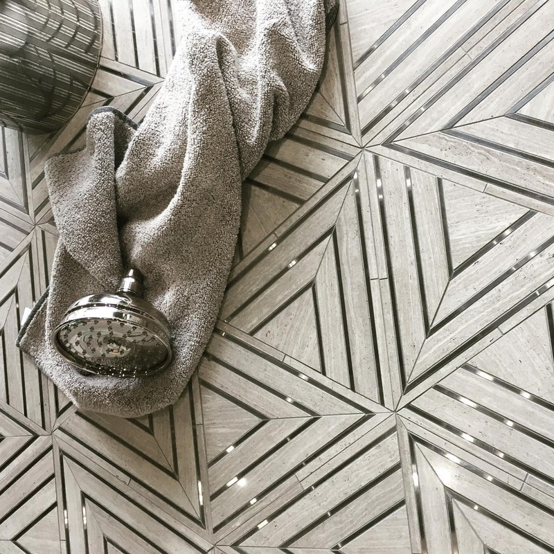 Triangle inspired stone mosaic flooring with metallic inlay creating multiple triangles in a graphic pattern in the bathroom. Made to order mosaic that can be created in whatever materials you choose