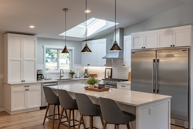 custom kitchen with skylight and long rectangular island, country-style cabints