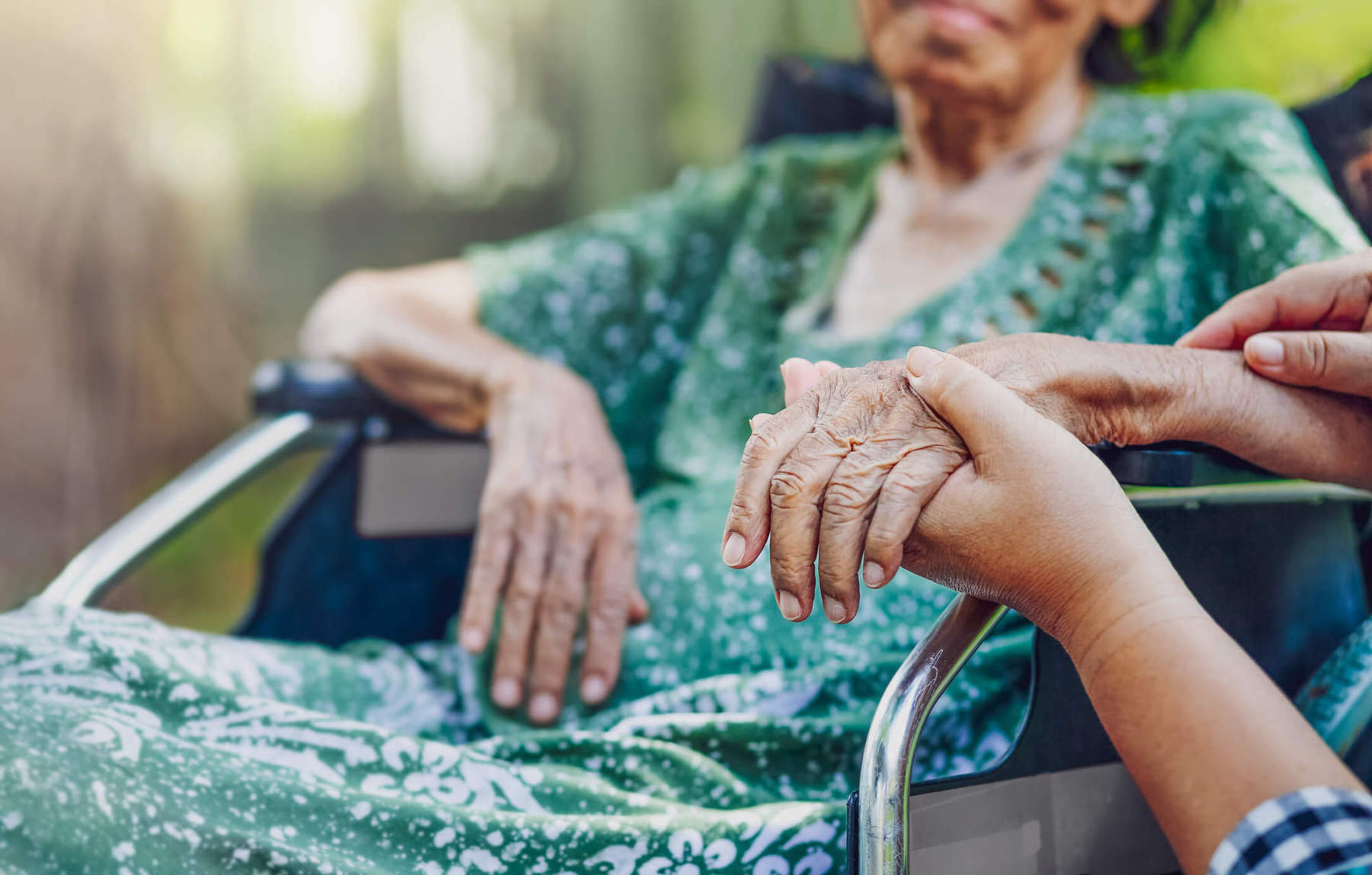 elderly woman wearing a green dress sits in a wheelchair holding hands with an unpictured person