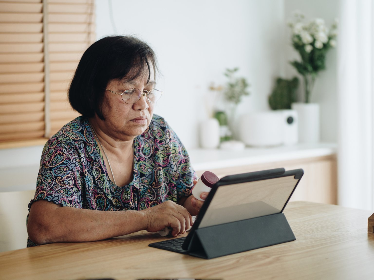 Asian senior woman sits at a wood table with digital tablet and checking prescription label