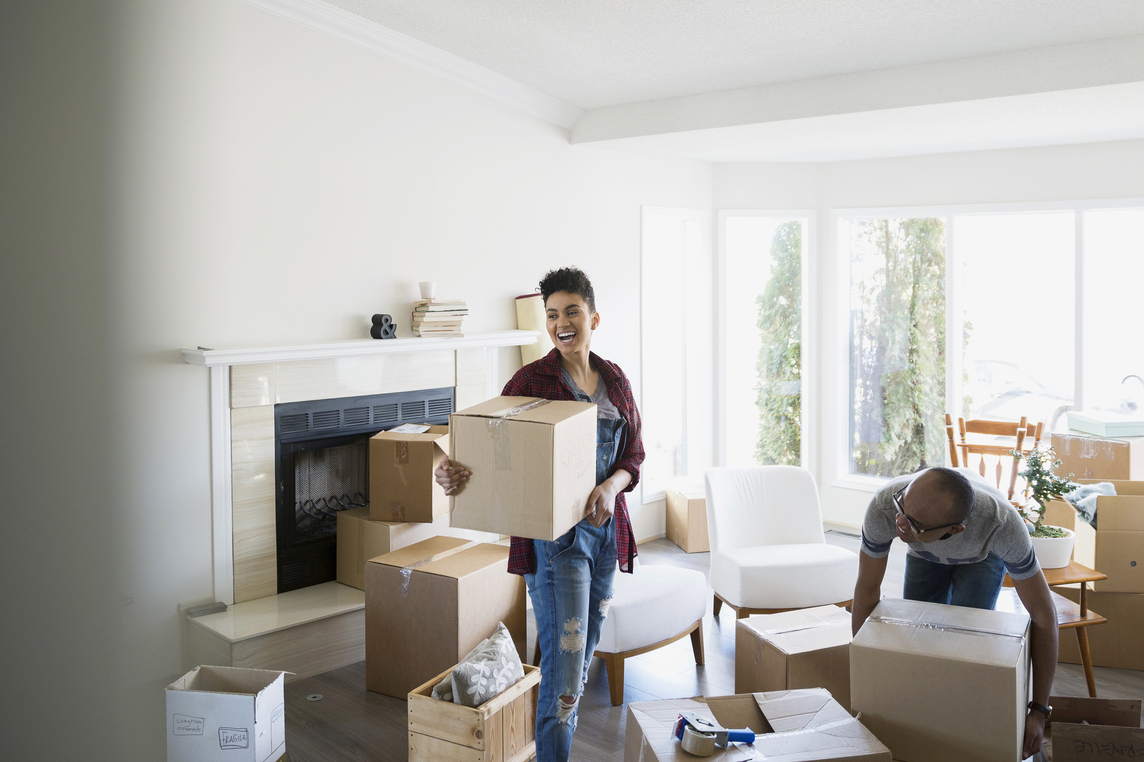 Image of two people inside their home with moving boxes