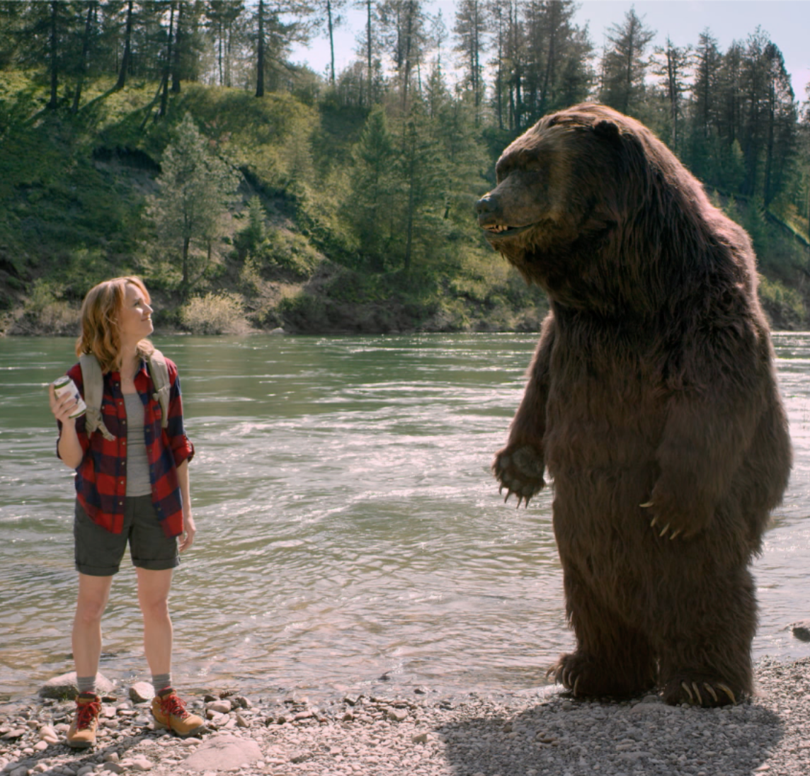 Woman hiker talking to a bear at the edge of a river