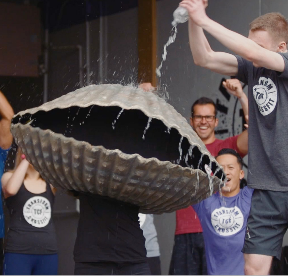 Person in a clam costume being cheered on by other members in a fitness class