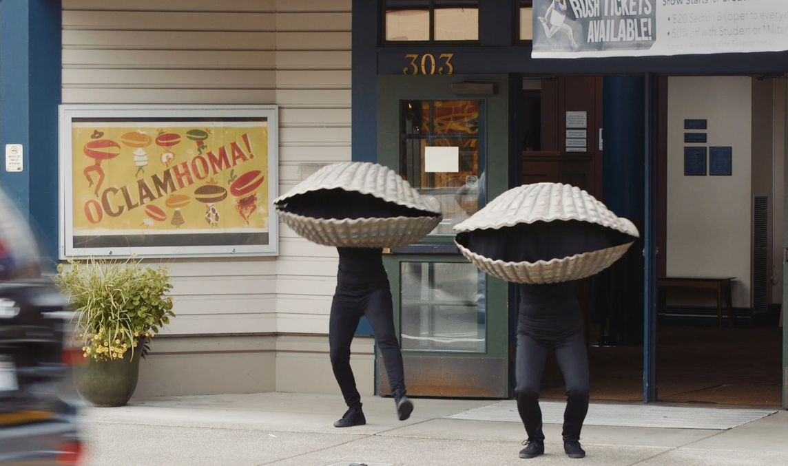 Two people in clam costumes leaving the theater