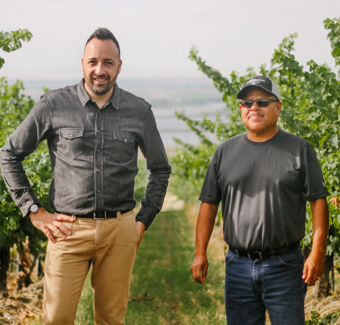 Two men standing outside in a vineyard
