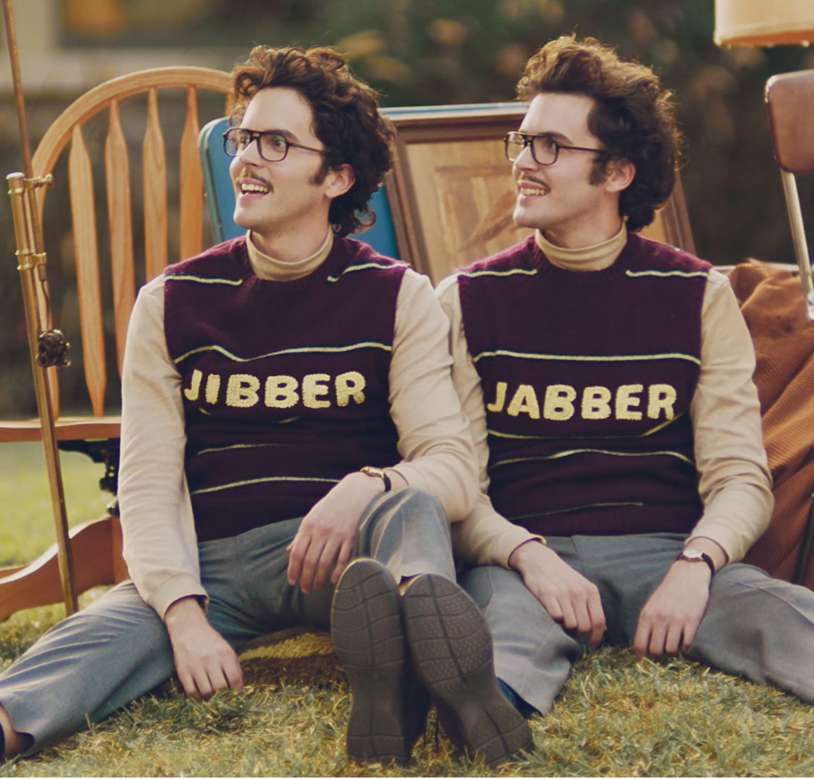 Two men with sweater vests reading Jibber and Jabber sitting on a lawn