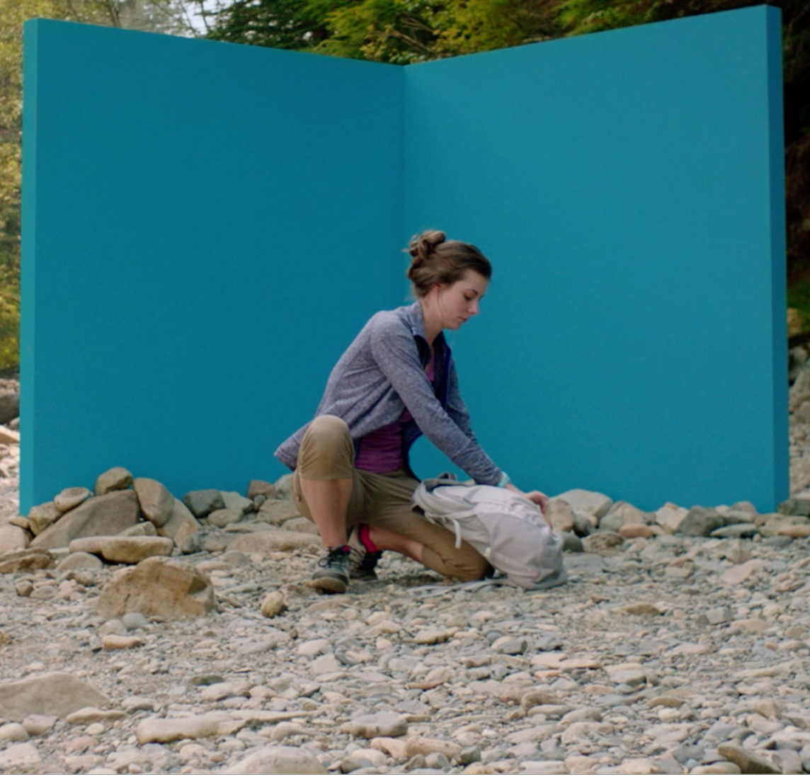 A woman on a hiking trail who stops in front of a five-foot-tall blue corner wall
