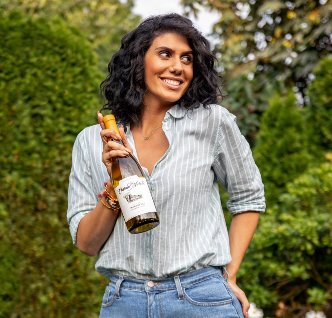 A woman walking toward camera and holding a bottle of wine
