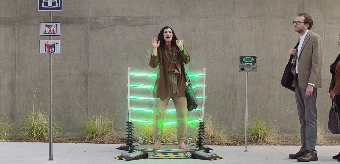 A woman standing in front of a teleportation device scared of what might happen