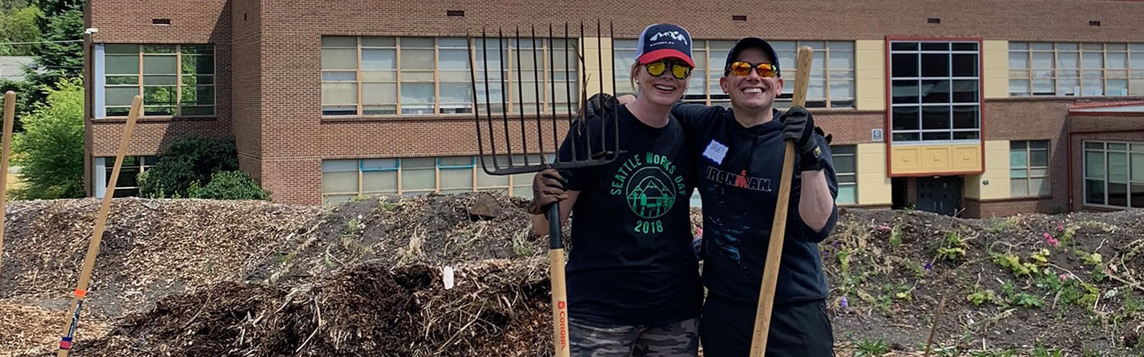 two Copacino Fujikado employees volunteering at a community farm during Seattle Works Day