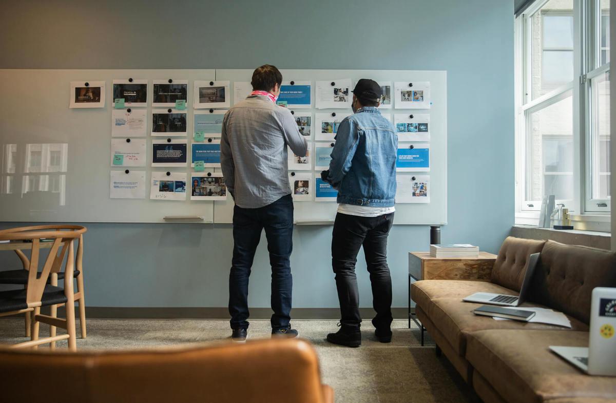 Copacino Fujikado creative team members evaluating work on the wall