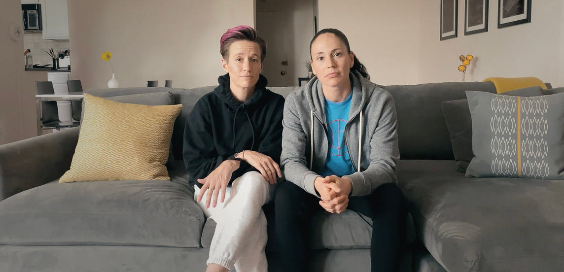 Photograph of Megan Rapinoe and Sue Bird sitting on a couch facing the camera