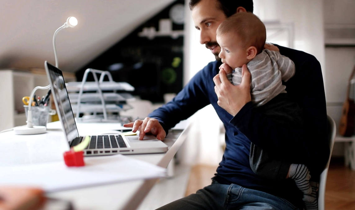 Image of a man in front of a laptop computer, working from home and holding a baby while working