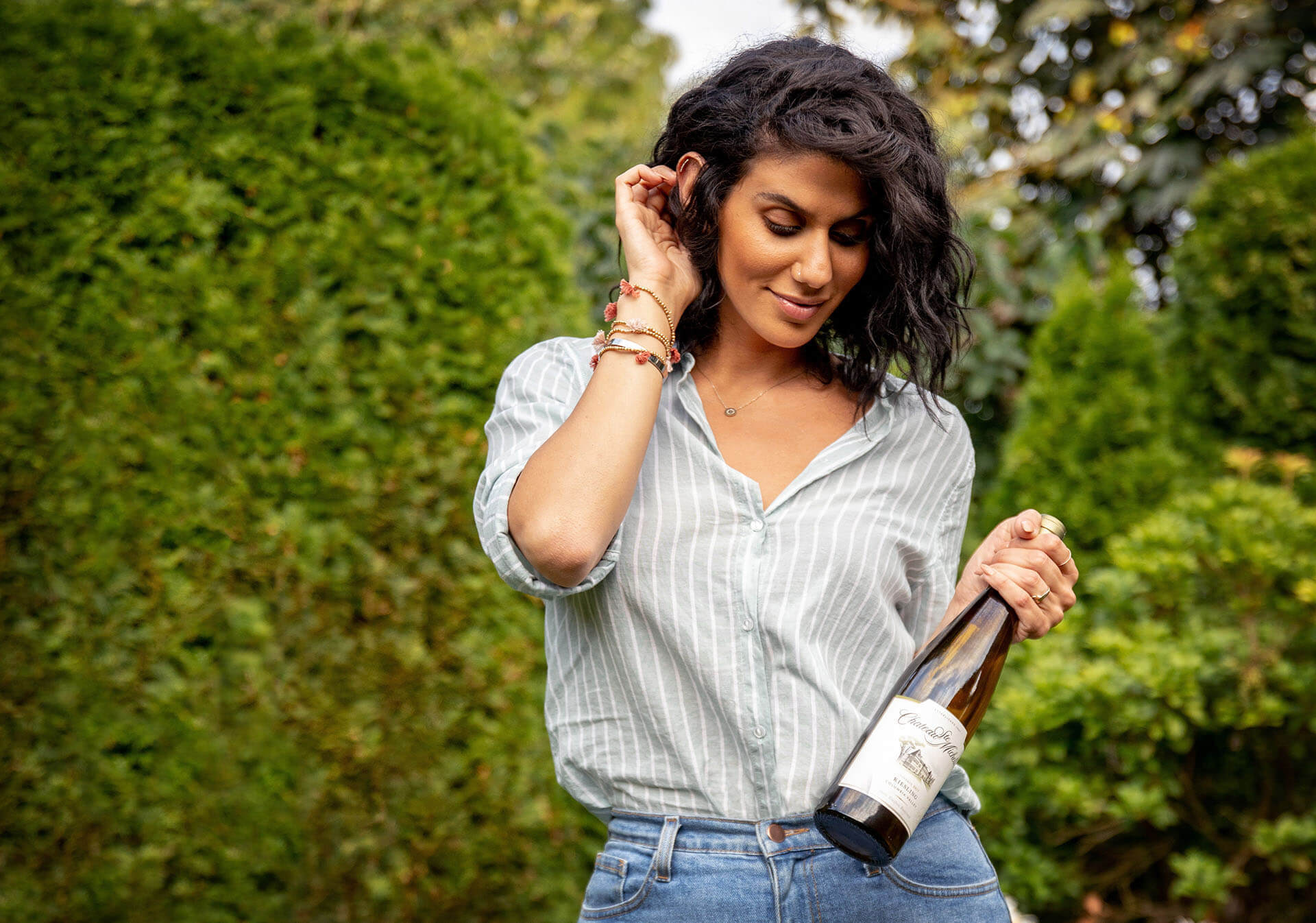 Photo of a woman arriving at a party with a bottle of wine