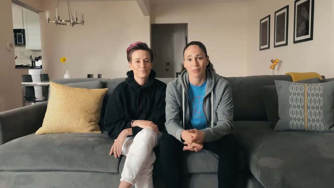 Megan Rapinoe and Sue Bird on a couch looking toward the camera