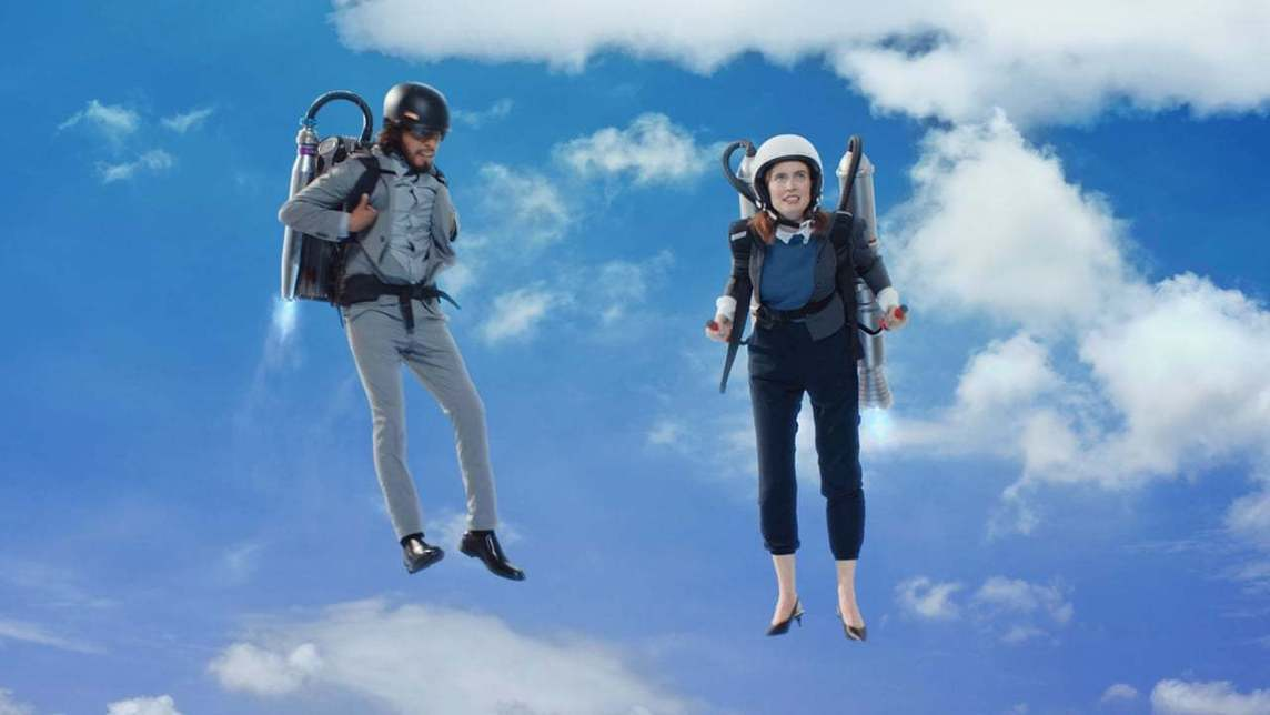 Two people in work clothes floating in the sky with jet packs