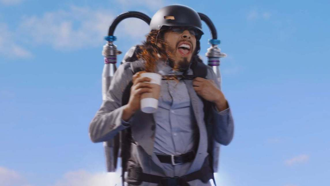 Man floating in sky wearing a jet pack and spilling his coffee