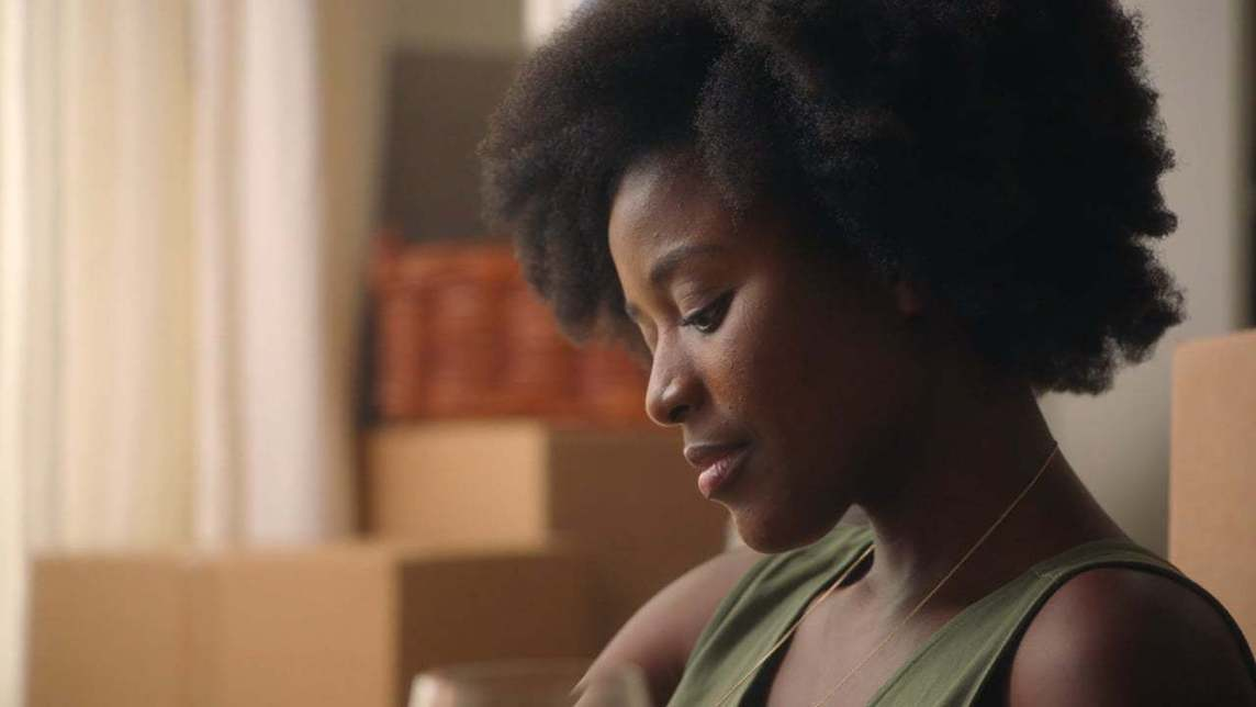 Profile view of a woman with moving boxes in the background