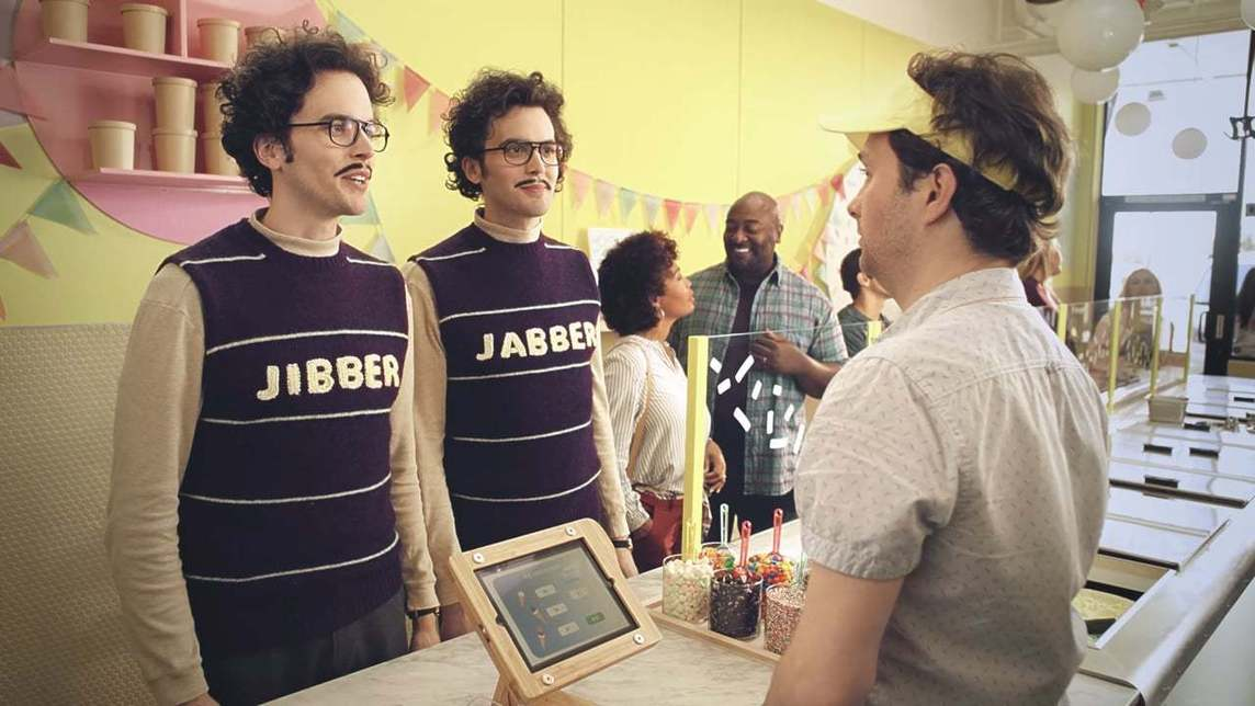 Two men with sweater vests reading Jibber and Jabber ordering ice cream