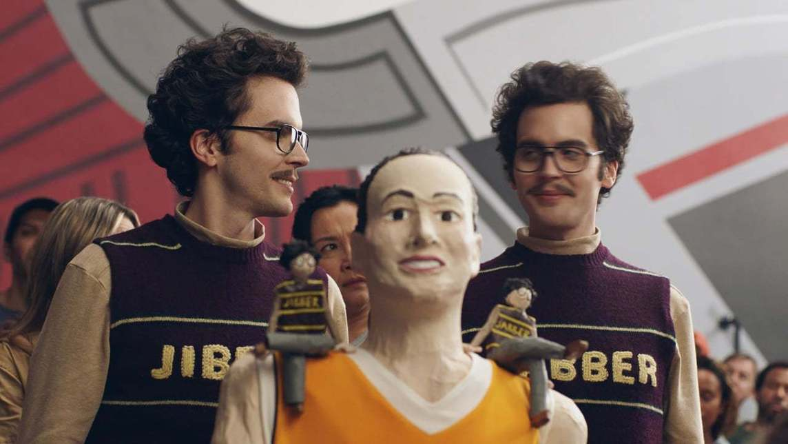 Two men in Jibber and Jabber sweaters behind a paper mache woman