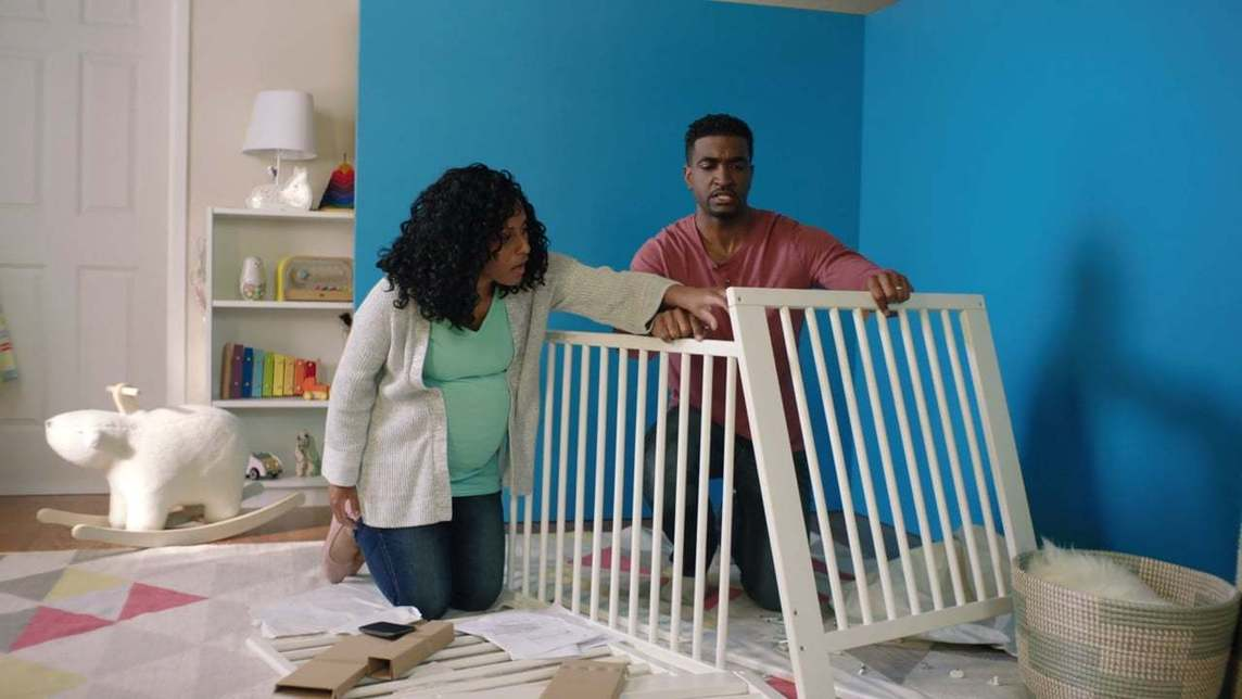 Couple assembling a baby crib in front of a blue corner wall