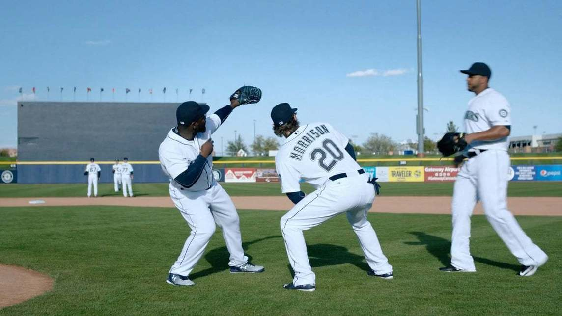Three Seattle Mariners players near the pitchers mound