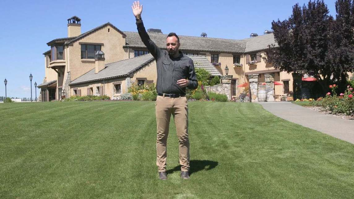 Man standing on a lawn waving hello
