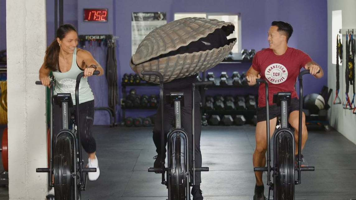 Person in a clam costume riding a stationary bike in a fitness class