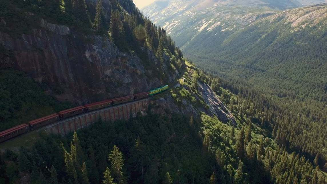 Wide view of Alaska mountains with train running along the mountainside