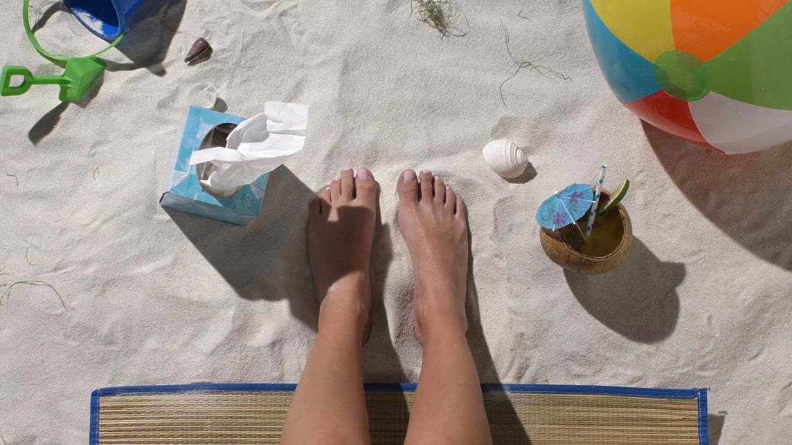Two feet in the sand next to a beach ball and box of tissues