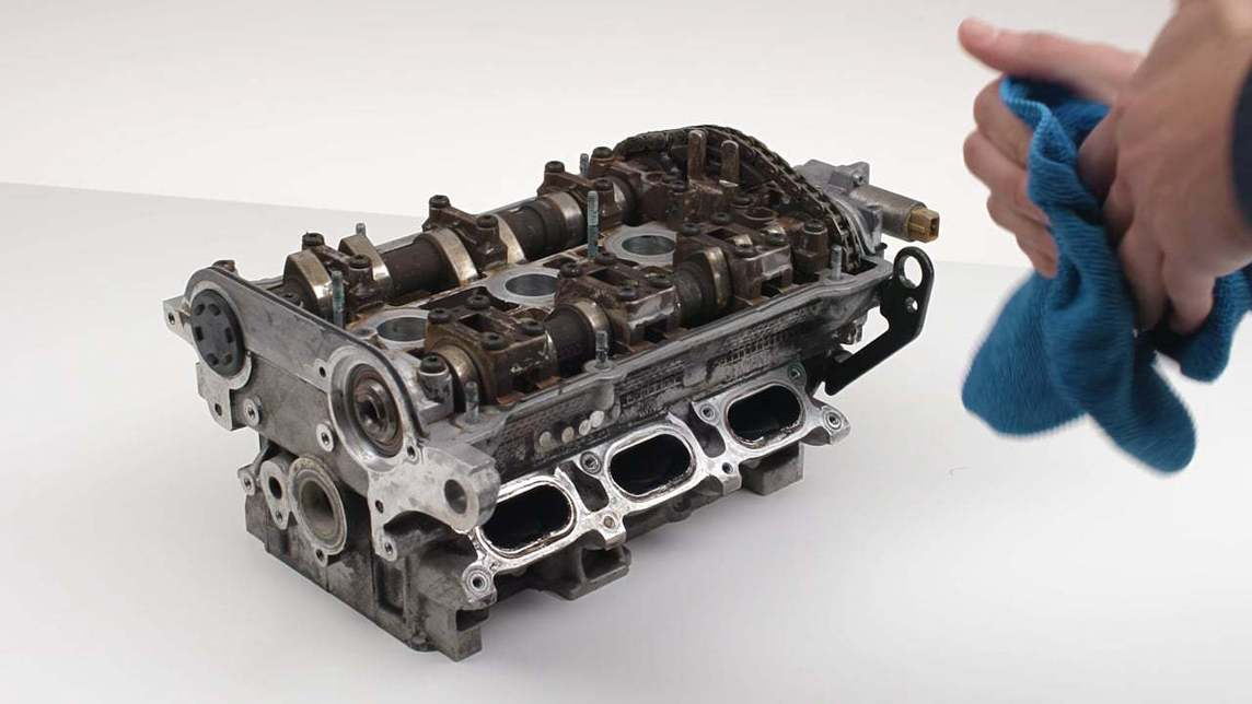 A car engine on a white background with hands in the foreground