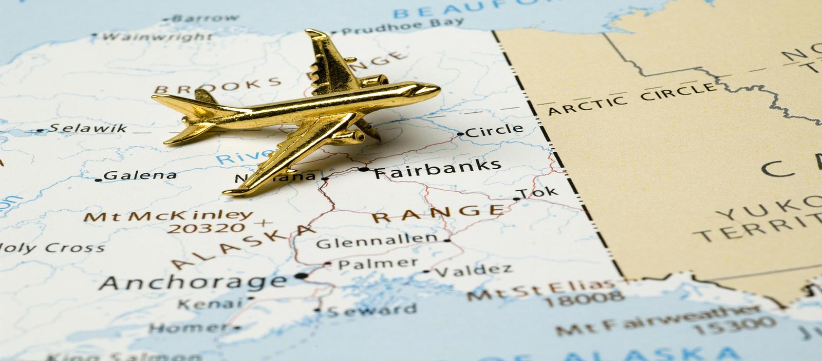 Plane figurine on map of Alaska