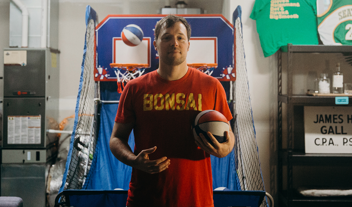 Andrew Gall standing in front of a basketball shooting game