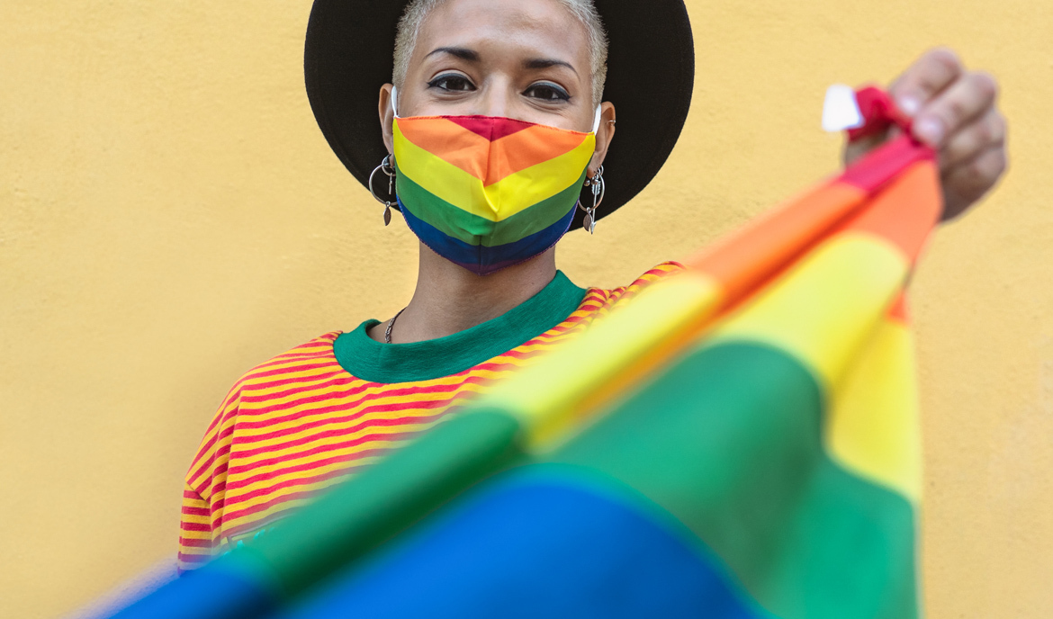 A person with a rainbow face mask, holding rainbow pride flag
