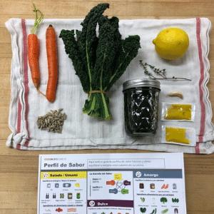 Carrots, Kale, sunflower seeds, lemon, a glass jar, mustard packets, and garlic clove on a towel