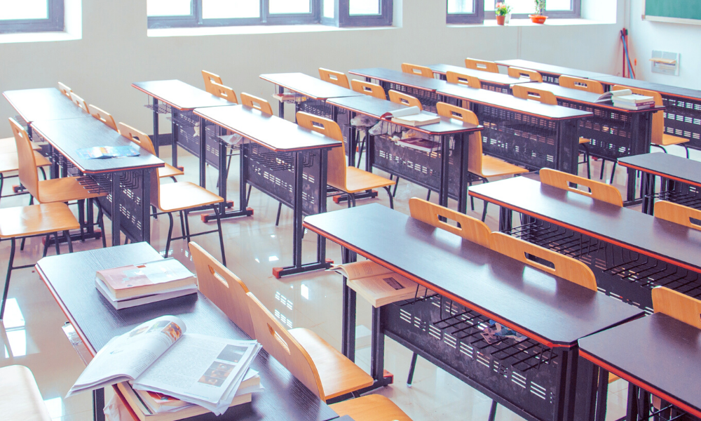 empty classroom with desks and school materials, open books on top