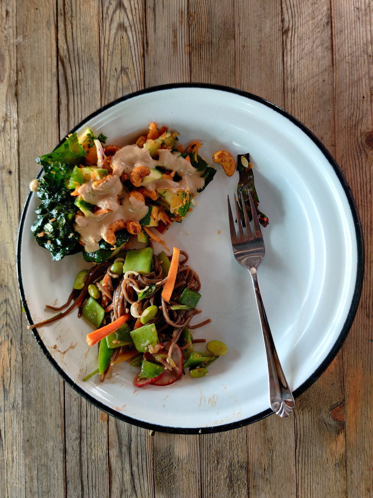 curry cashew and carrot salad and soba noodle salad with ginger soy sauce on a plate.