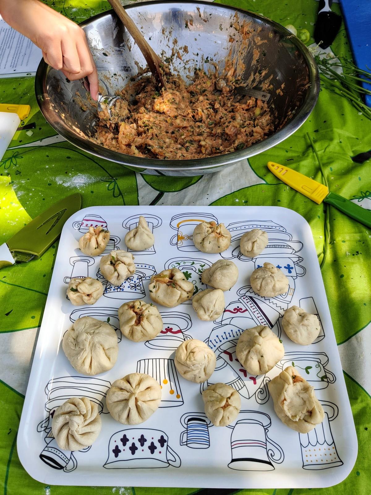 a pan of dumplings with a bowl of dumpling mix behind them.