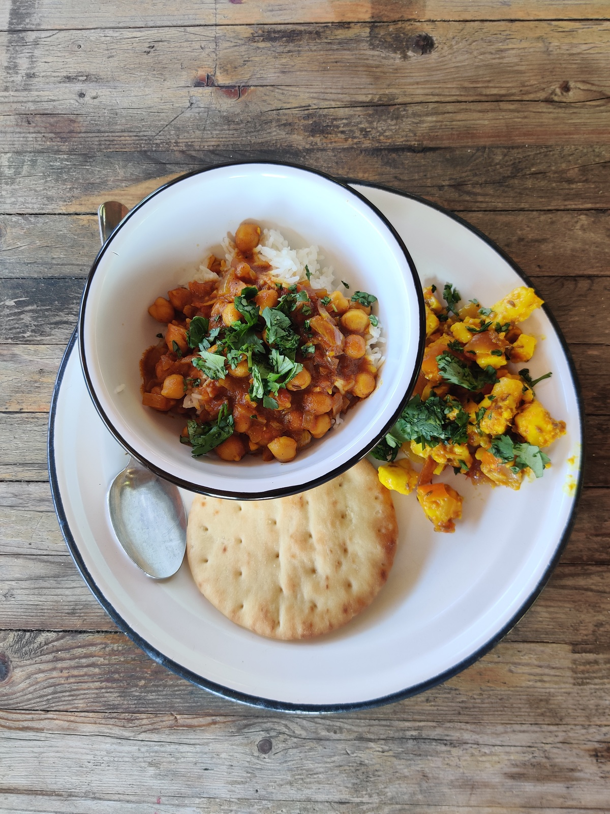 a bowl of chole over rice on a plate with bread and salad.