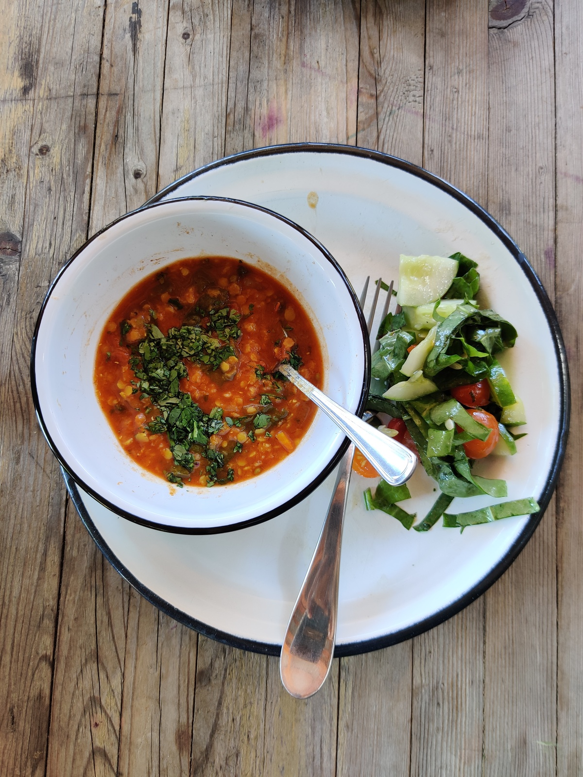 bowl of lentil soup with cilantro on a plate with salad on the side.