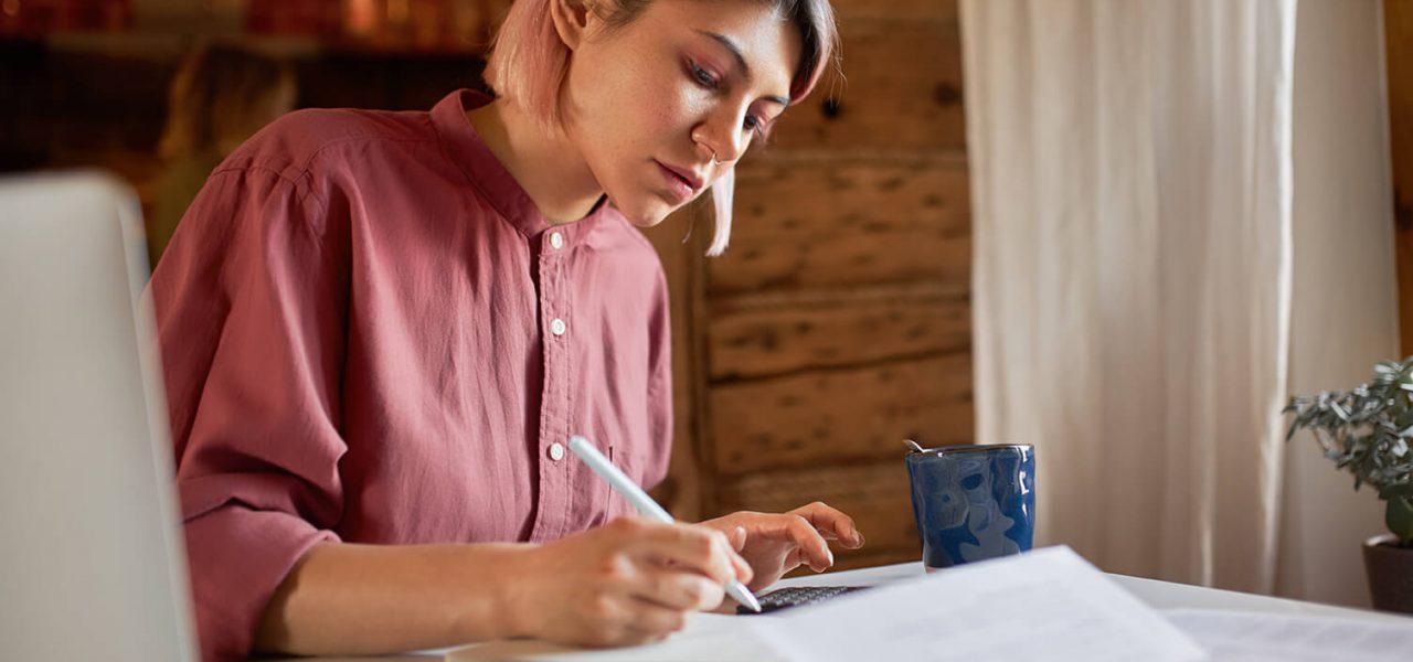 Imagem de uma jovem empreendedora com seu computador sobre a mesa e alguns papéis, onde ela está escrevendo