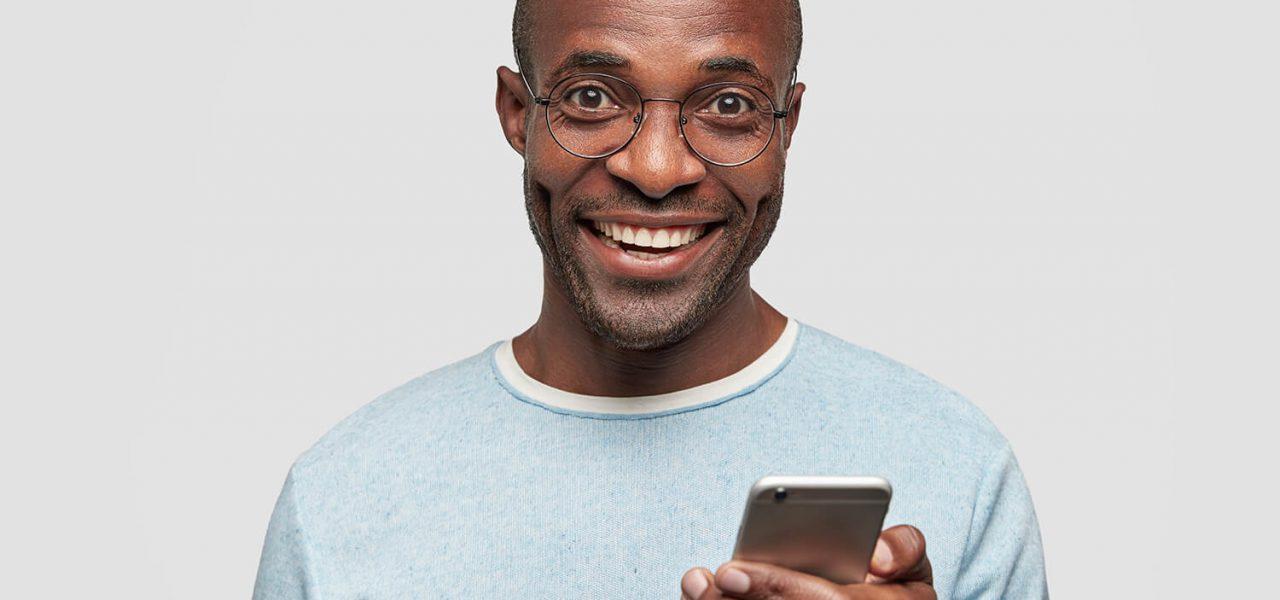 Fotografia de um homem sorrindo com um celular na mão