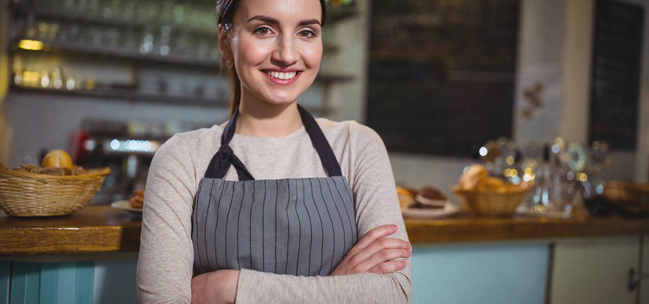 Foto de uma mulher morena, de braços cruzados, utilizando um avental na frente do balcão de uma cafeteria