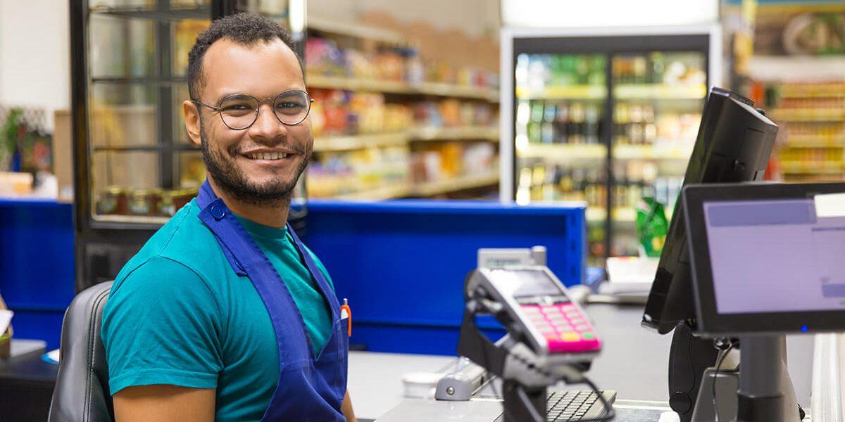 Foto de um homem sorridente no caixa de um mercado