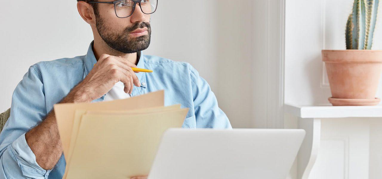 Homem sentado em frente ao computador, analisando documentos